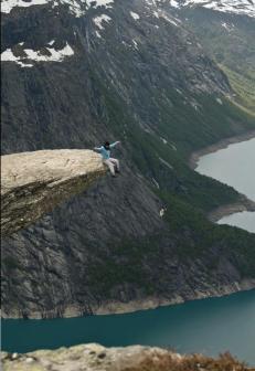 Sitting on the Trolltunga rock in Norway