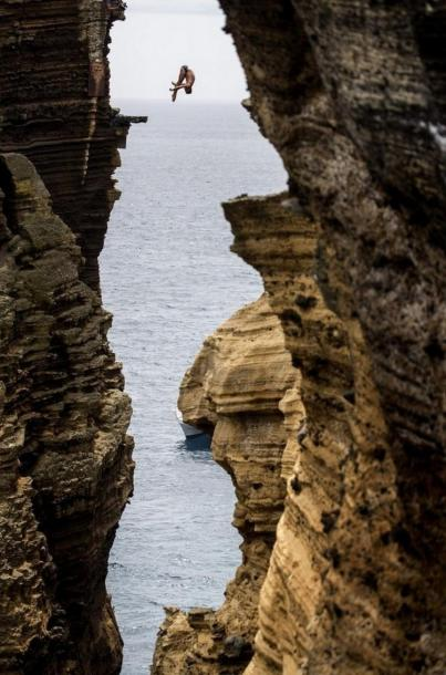 Blake Aldridge dives 29 metres from the rock monolith during the Red Bull Cliff Diving World Series in Portugal